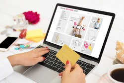 Woman shopping online on her laptop and holding credit card in hand