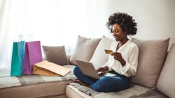 Woman shopping online while chilling at home on the sofa. I have enough cash to spend. Happy girl with shopping bags. Cropped shot of a woman using her credit card to make an online payment