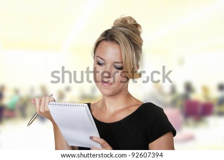 woman shot in the studio on white background holding a pen and note book talking notes