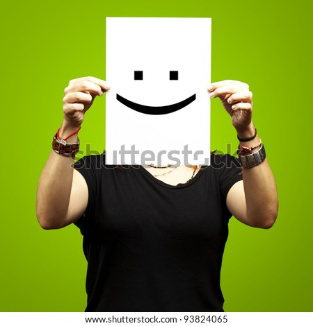 Woman showing a blank paper with a smile emoticon in front of her face against a green background - stock photo