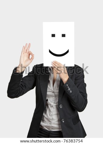 Woman showing a happy emoticon in front of face and making a okay gesture with the right hand