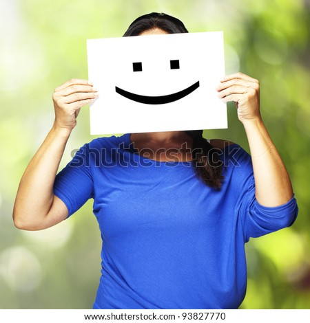 Woman showing a happy emoticon in front of her face against a nature background