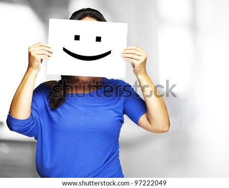Woman showing a happy emoticon in front of her face indoor