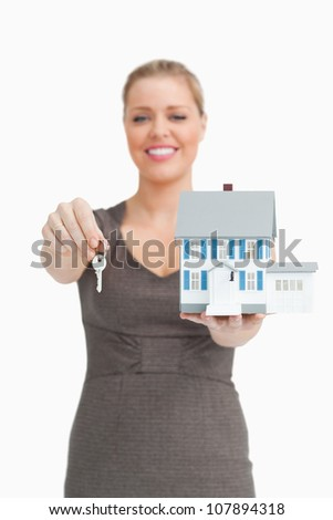 Woman showing a key and a model house against white background