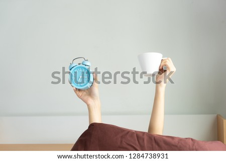 Woman showing arm raised up holding coffee cup and blue alarm clock behind duvet in bed room. Young girl with two hands sticking out of blanket. wake up with fun in morning concept.