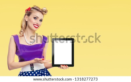Woman, showing blank no-name tablet pc monitor, dressed in pin-up style dress in polka dot, with copy space area for some slogan or advertising text message, on yellow background. Retro and vintage.