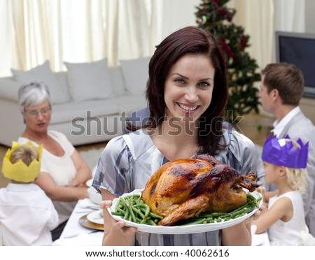 Woman showing Christmas turkey for family dinner at home