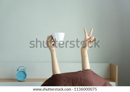 Woman showing funny victory sign and holding cup behind blanket in the bed room, Young girl with two hands sticking out from the duvet. wake up with fun in morning concept.