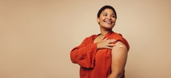 Woman showing her arm after receiving vaccine shot on brown background. Female with bandage on her arm looking away and smiling.