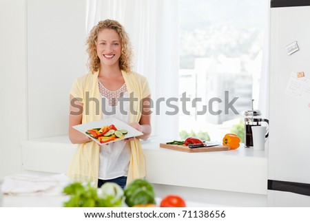 Woman showing her healthy food  in her kitchen at home