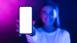 Woman showing phone with blank screen in neon lights, stretching cellphone to camera, free space