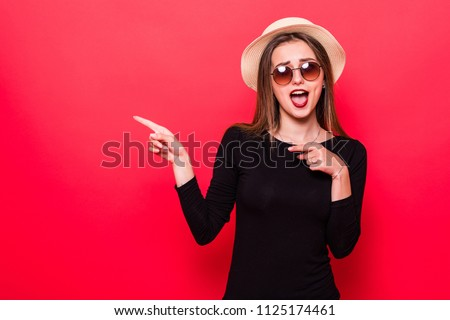 Woman showing pointing on red background. Very fresh and energetic beautiful young girl smiling happy presenting on red background.