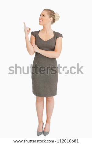 Woman showing something with her finger against white background