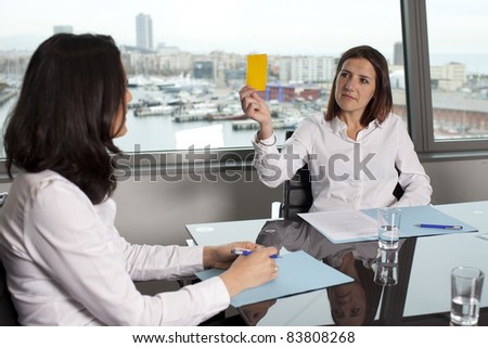 Woman showing the yellow card as warning in office