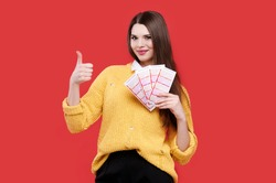 Woman showing thumb up gesture and holding lottery tickets, isolated red background