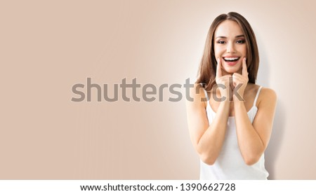 Woman showing toothy smile. Portrait of happy optimistic girl. Beige color background with blank wide Copy Space area, for some advertising text or slogan. Optimism or Dental Health Care concept photo