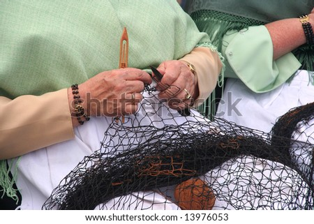 Woman showing traditional skill of repairing fishing net