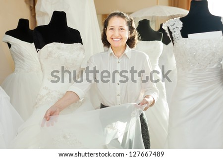 Woman shows bridal gown at shop of wedding fashion