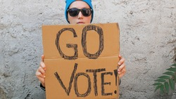 Woman shows cardboard with Go Vote sign on brick wall urban background. Voting concept. Make the political choice, use your voice. Young lady in blue hat invite to go to the presidential elections.