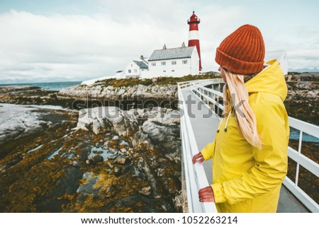 Woman sightseeing Norway lighthouse landscape Travel Lifestyle concept adventure tourist at vacations outdoor girl wearing yellow raincoat standing alone #1052263214
