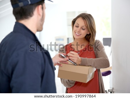Woman sigining electronic receipt of delivered package