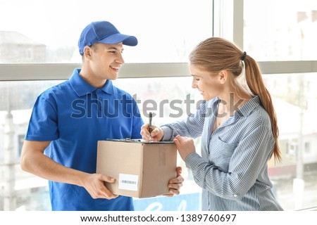 Woman signing documents to confirm receiving of order from delivery company #1389760697
