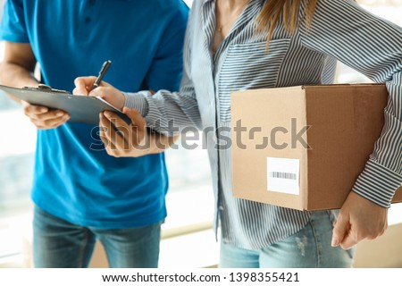Woman signing documents to confirm receiving of order from delivery company #1398355421