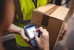 Woman signing on device to delivery parcel by van