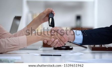 Woman signing vehicle purchase agreement, taking car keys from dealer, insurance Stockfoto ©