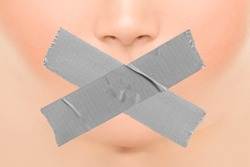 Woman silenced with adhesive duct tape covering closed mouth. Censorship, shut down of freedom of speech. Face nose and lips.