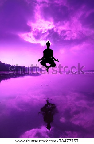Woman Silhouette doing yoga padmasana lotus posture in jumping on the beach at the sunset in purple color