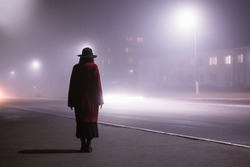 Woman silhouette on background of the night city in fog. Thick mist in dark scary evening city. Dark noir silhouette in hat on background of fog. Alone woman in mist. Noir mystery film. Lost man