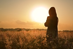 Woman silhouette waiting for summer sun on meadow