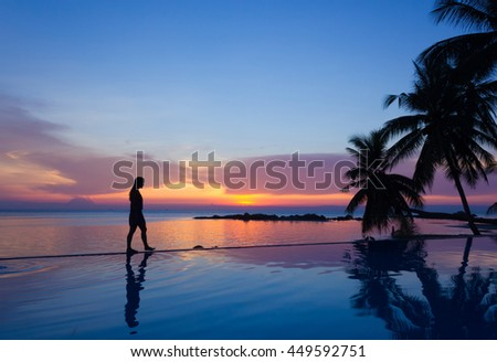 Woman silhouette walking over infinity pool at sunset in the island of Koh Phangan, Thailand. Vacation resort, tropical holidays exotic destination concept #449592751