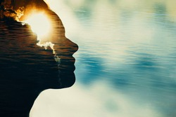 Woman silhouette with sun in head with copy space. Multiple exposure image.