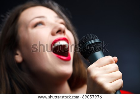 Woman sing over dark background. focused on hand.