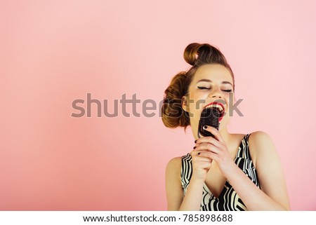 Woman singer with stylish retro hair and makeup. Girl in glasses sing in microphone. Beauty and vintage fashion. Pin up young girl on pink background, radio. Music, look and retro style, pinup. #785898688