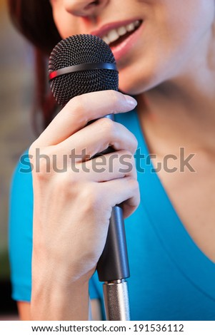 Woman singing karaoke. Closeup of woman singing into microphone