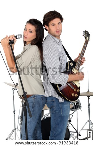 Woman singing whilst man plays guitar