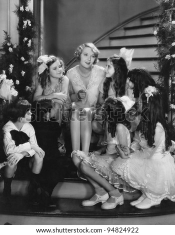 Woman singing with children on staircase at Christmas