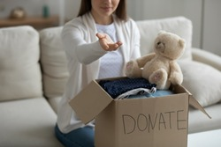 Woman sit on sofa with her arm stretched out as symbol of needy person need for humanitarian help, donation box full of clothes and stuffed toy on table. Concept of old belongings prepared for charity