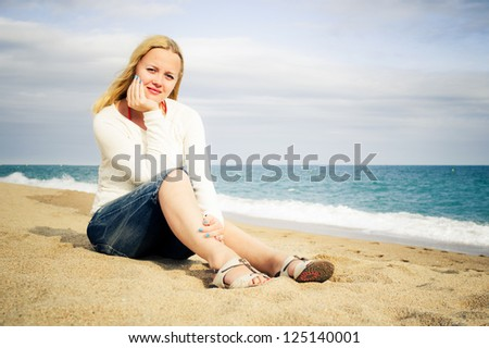 woman sit on the beach by the sea wearing jeans