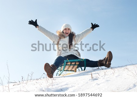 Woman sits and sledges from the mountain against the background of snow and sky in winterGirl laughs and rejoices in snow, entertainment in the sled. Stock photo ©