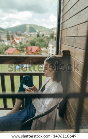 Woman sits in a chair on a balcony in an apartment and uses a smartphone. Portrait of a girl sitting in a country house on a wooden balcony and concentrated looks at the screen phone.Vertical photo