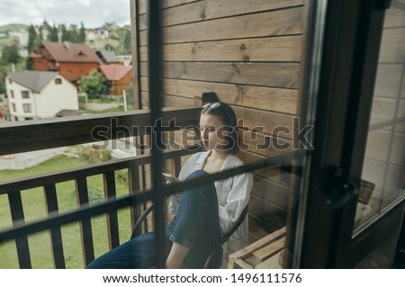 Woman sits in a chair on a balcony in an apartment and uses a smartphone. Portrait of a girl sitting in a country house on a wooden balcony and concentrated looks at the screen smartphone.