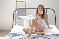 woman sits in bed with cup of hot drink