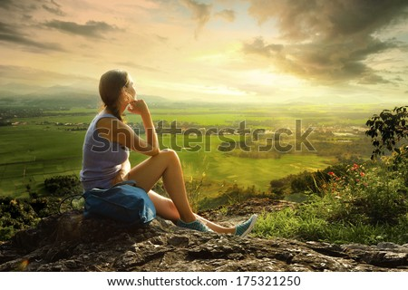 Woman sits on edge of cliff and looking at sun valley and mountains