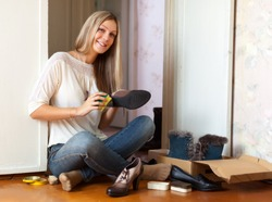 Woman sits on floor and cleans shoes