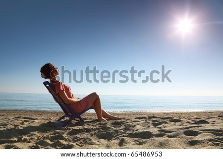 Woman sits on  plastic chair on  sea-shore by  person to  sun and becomes tanned, heaving up  head