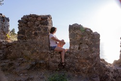Woman sits on the fortress wall in Alanya fortress, Turkey